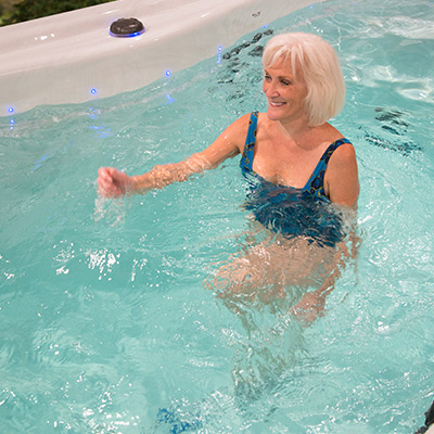 Woman doing resistance training in H2X Swim Spa